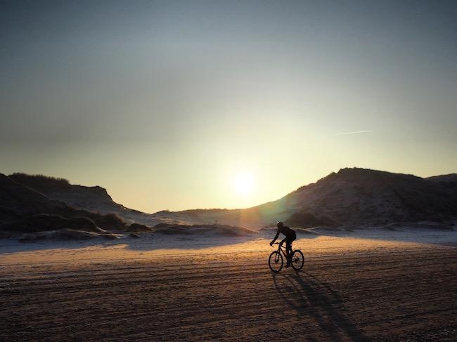 Zonsopgang en een mountainbiker over het strand in Egmond tijdens het wandelen in Nederland